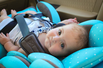 little girl sits in the car seat