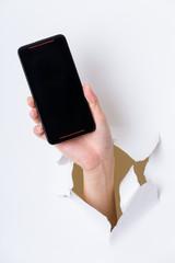 Hand holding mobile phone bursting through paper