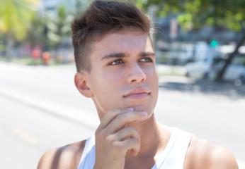 Sportlicher junger Mann schaut verträumt
