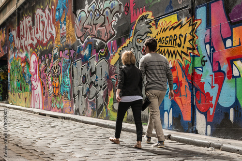 Poster, Tablou young couple walking past graffiti wall in Melbourne
