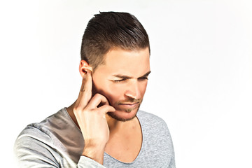 Depressed young man covering ears with hands isolated on white b