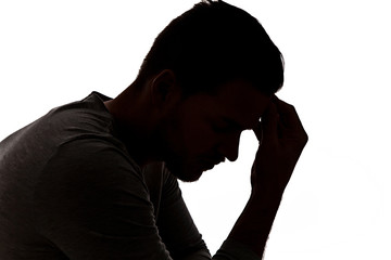Desperate young man in silhouette holding his head