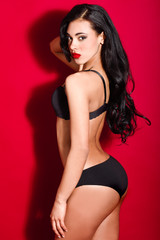 Latin woman wearing black lingerie on red background