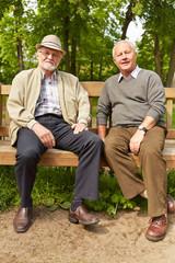 Zwei Senioren sitzen auf Bank im Park