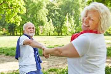 Glückliche Senioren drehen sich im Sommer