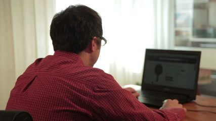 Male using laptop for searching on website. Monitor blurred