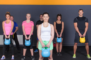 crossfit fitness group of people holding kettlebells