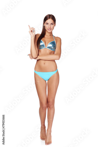 Woman in blue bikini pointing to copy space - 79433666