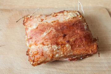 Roast meat lies on a wooden board
