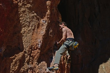 Powerful male climber climbing rock face