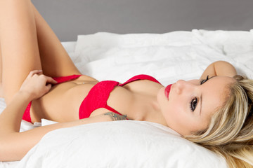 Blonde beautiful woman with red lingerie in the bed