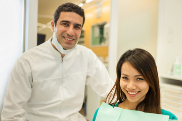 smiling caucasian dentist with beautiful asian woman looking tow