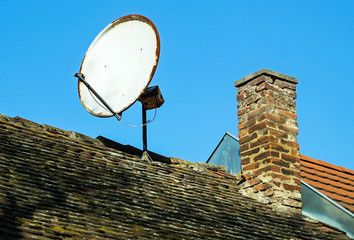 Rusty satellite dish on the roof of an old building