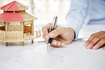 Closeup of architect showing drawing plan