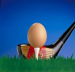 Palo de golf golpeando una pelota huevo.Golf conceptual.