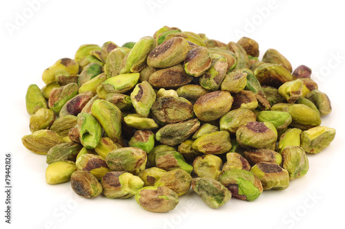 bunch of dried pistachio nuts on a white background - 79442826