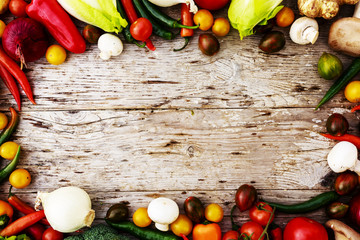 Frame of various vegetables over a rustic wooden background with