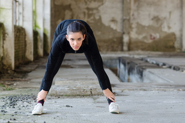Beautiful young girl working out in abandoned building
