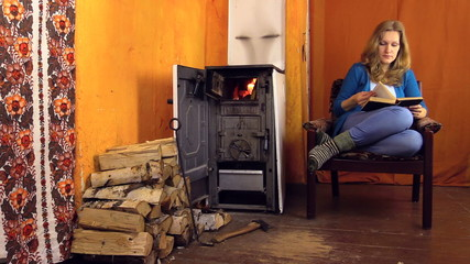 Woman sit on armchair at home, read book near stove