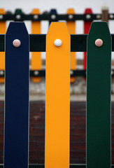 Close view of colorful painted playground fence.