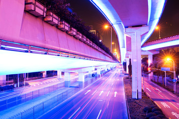 illuminated traffic on elevated expressway in modern city.