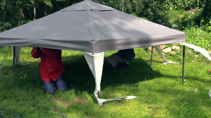 men crawled under gazebo canvas top fix on metal structure