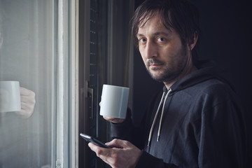 Drinking Coffee And Texting with Mobile Phone in Morning