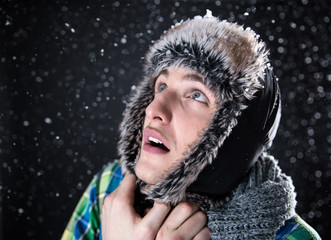 Surprised young man looking up with snow on background