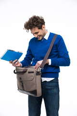 Smiling young man standing with bag and notebook
