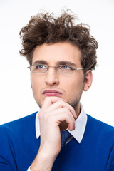 Pensive young businessman in glasses looking up