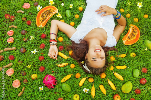 woman lying on a grass with the pattern of colorful fresh exotic - 79447673