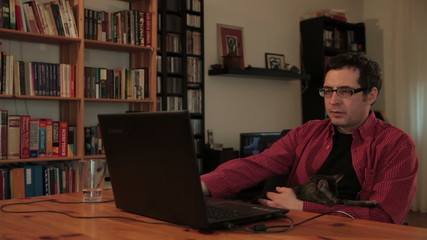 Man with cat sitting on chair and typing on laptop computer