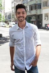 Modischer junger Mann steht in der Stadt