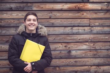 Junger lachender Schüler mit Mappe vor Holzwand