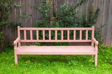 Old red park bench stands on green grass