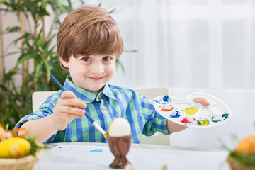 Beautiful smiling child painting eggs wth brush and holding colo