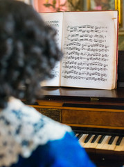 Portrait of woman playing vintage piano.