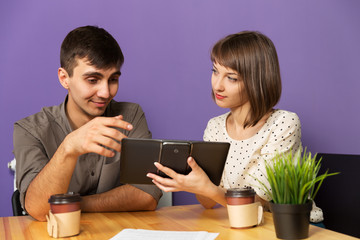 Young couple with tablet computer sitting at the table