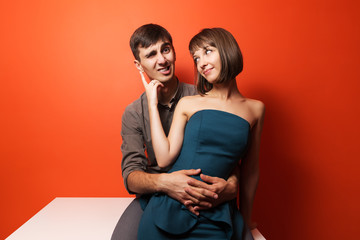 Happy young couple sitting on the desk
