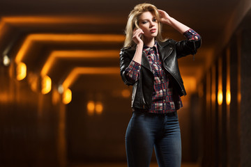 Young fashion blond woman in leather jacket calling on phone