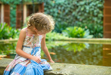 Little girl sitting by the pond with fish.