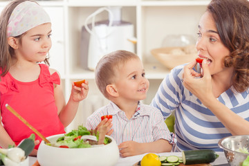 Mother and two children preparing vegetable salad