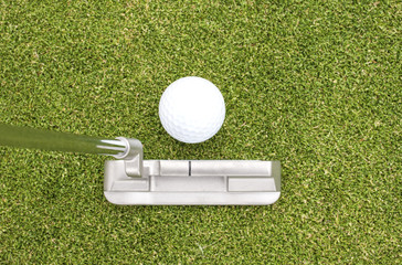 Putter and golf ball on green.