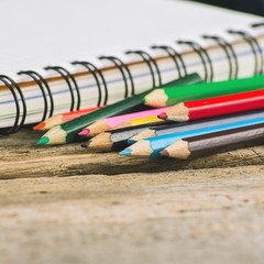 Checked blank notebook with multicolored pencils
