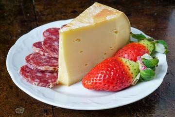 Fontina, salame e fragole su piatto tavolo e sfondo nero