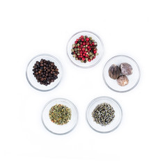 five different kind of dry spices on glass cups from above