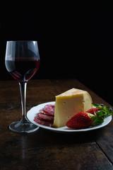 Piatto Fontina, salame, fragole e vino rosso sfondo nero
