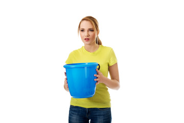 Young woman holding blue bucket.