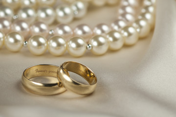 Pair of gold wedding rings again pearl background (Shallow DOF)