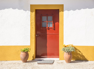 white and yellow country house with a red door